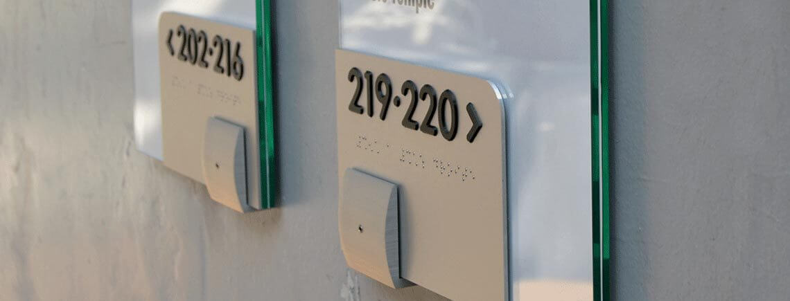 wall-mounted signpost signage with raised text and braille | opalescent© marcal