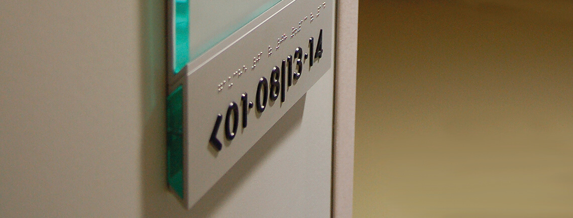 wall-mounted sign post with tactile and Braille writing, for DDA and ADA compliant signs| pile-ou-face© marcal